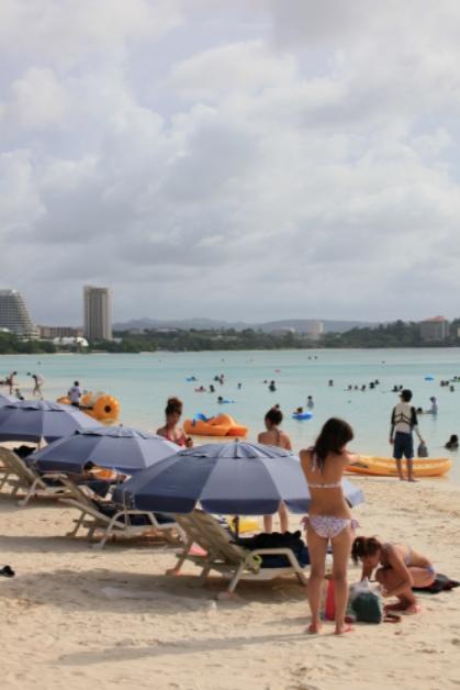 日焼け止めをぬる女性とグアムのビーチ